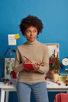 Indoor shot van contemplatieve afro-amerikaanse vrouw houdt dagboek