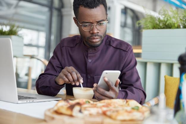 Indoor shot van donkere huid ernstige jonge afrikaanse mannelijke ondernemer gericht op scherm van mobiele telefoon, drinkt latte, leest aandachtig nieuws op internetwebsite