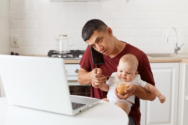 Indoor shot van een drukke brunette man met een kastanjebruin t-shirt in casual stijl, zittend aan tafel in de keuken, zijn dochtertje voedend met fruitpuree, pratend via mobiele telefoon kijkend naar laptopscherm.