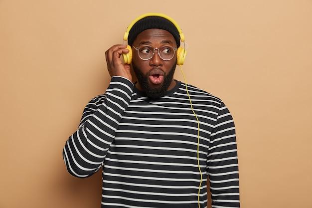 Indoor shot van emotioneel geschokt bebaarde man luistert moderne muziek in koptelefoon, kijkt met een verbijsterde uitdrukking, verbaasd geluid verdween