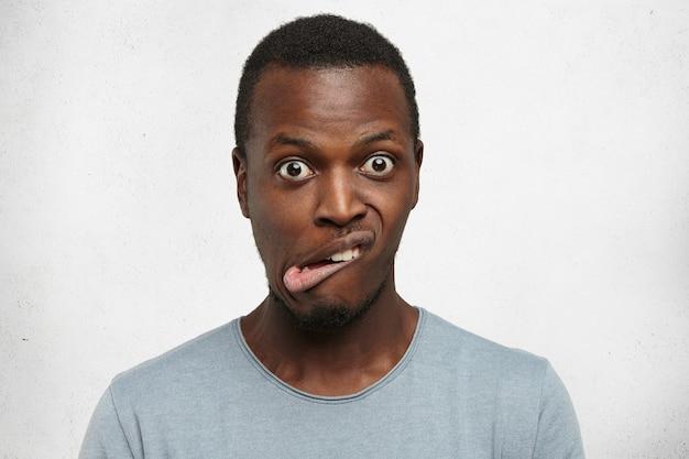 Indoor shot van emotionele jonge donkerhuidige man in grijs t-shirt grimassen, ogen uitluisteren