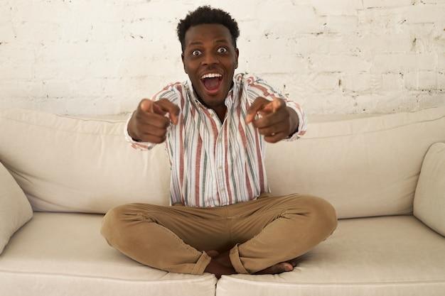 Indoor shot van emotionele knappe jonge donkere man die ware opwinding en plezier uitdrukt