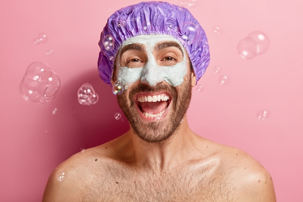 Indoor shot van emotionele tevreden man met kleimasker, geniet van het nemen van een douche en gezichtsbehandeling, draagt een badmuts, zeepbellen vliegen rond, wast het lichaam