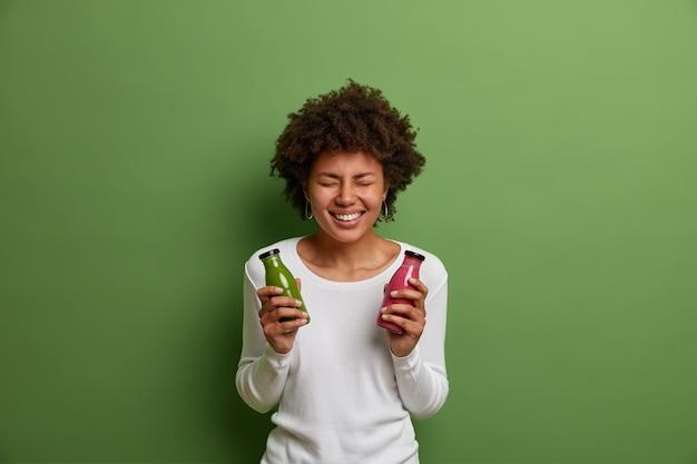 Indoor shot van erg blij lachende vrouw houdt flessen gemengde spinazie en aardbei smoothie, geniet van detox drank drinken, poses met vers bereide verse drank, geïsoleerd op groene achtergrond