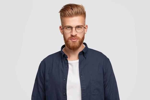 Indoor shot van ernstige roodharige jongere heeft dikke gemberbaard, snor, ziet er zelfverzekerd uit, draagt een modieus shirt, heeft een specifiek uiterlijk