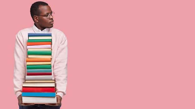 Indoor shot van geconcentreerde jonge zwarte man gefocust opzij, draagt veel boeken, merkt iets op