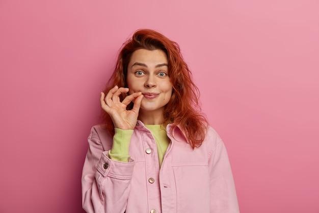 Indoor shot van geheime roodharige jonge vrouw ritst haar mond dicht, belooft geheim te houden, roddelt veilig, houdt vingers bij de wang