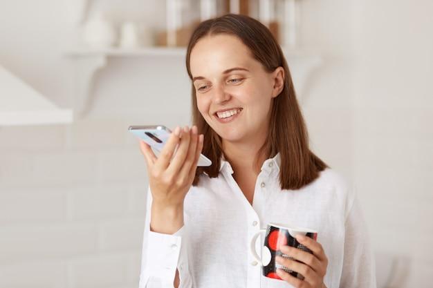 Indoor shot van gelukkig lachende jonge volwassen vrouw met smartphone en kopje koffie of thee in handen, gekleed in een wit casual stijl shirt, kijkend naar de weergave van de mobiele telefoon.