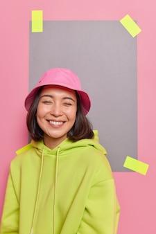 Indoor shot van gelukkig schattig aziatisch tienermeisje glimlacht aangenaam geniet van grappige conversatie grijns aan de voorkant gekleed in casual kleding poses tegen roze muur gepleisterd papier