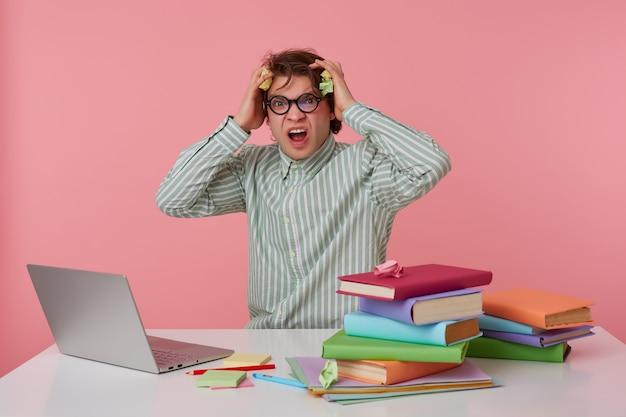 Indoor shot van gestrest jonge donkerharige man poseren in gestreept shirt, zittend aan de werktafel met veel boeken, zijn hoofd geklemd met een gefronst gezicht