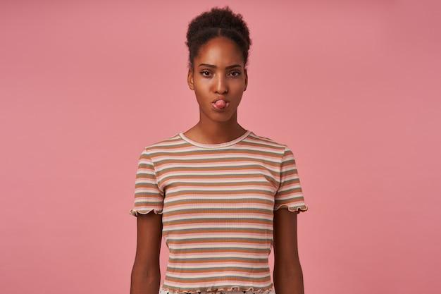 Indoor shot van jonge bruinharige krullende vrouw met knot kapsel met tong terwijl ze naar de voorkant kijkt, gekleed in beige t-shirt terwijl ze poseren over roze muur