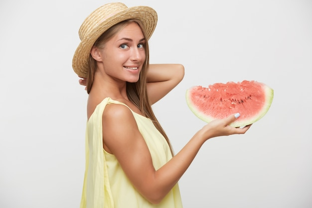 Indoor shot van jonge mooie langharige blonde dame kijkt positief over haar schouder terwijl ze watermeloen vasthoudt, licht glimlachend terwijl staande op witte achtergrond