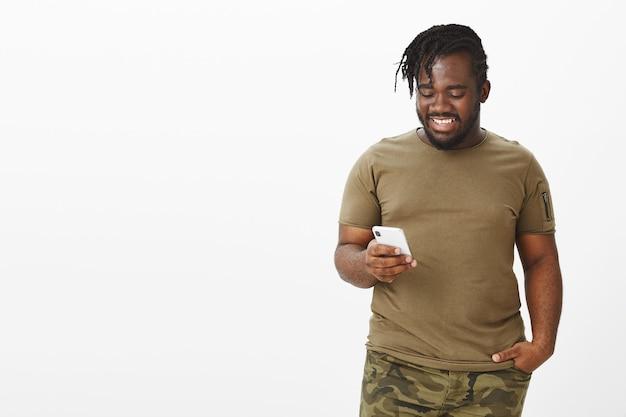 Indoor shot van knappe, gelukkige man in een bruin t-shirt poseren tegen de witte muur met zijn telefoon