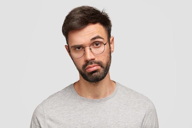 Indoor shot van knappe ongeschoren jongeman heeft aarzelende uitdrukking verveeld, trekt verbijsterd wenkbrauw op