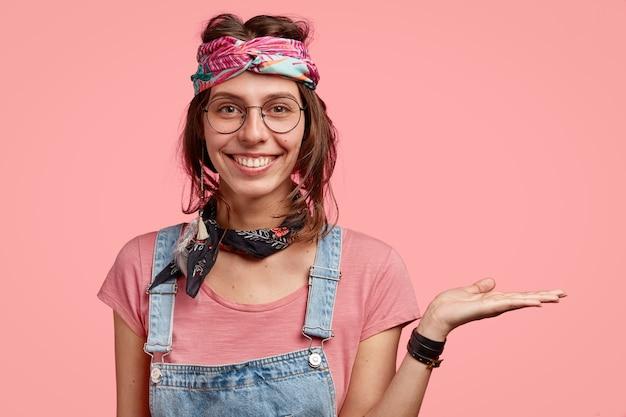 Indoor shot van lachende hippie draagt stijlvolle hoofdband en bril houdt kopie ruimte