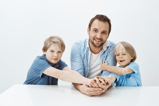 Indoor shot van mooie gelukkige vader en zonen aan tafel zitten en breed glimlachend, hand in hand en starend met een brede glimlach, gek rond