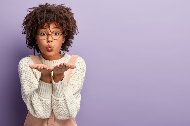 Indoor shot van mooie mooie gemengde race vrouw blaast luchtkus, strekt handen in de buurt van de mond, houdt de lippen gevouwen, nonchalant gekleed, staat over de paarse muur met vrije ruimte voor uw promotie