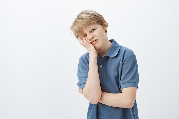 Indoor shot van ontevreden ongelukkige jonge jongen met blond haar in blauw t-shirt, gezicht palm en grimassen maken, geïrriteerd of beu zijn met huiswerk