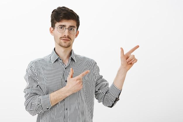 Indoor shot van onzekere volwassen kaukasische bebaarde man met snor in trendy ronde bril, naar rechts wijzend met een vingerpistoolgebaar, nieuwsgierig wenkbrauw optrekken, onzeker zijn terwijl hij richting wijst