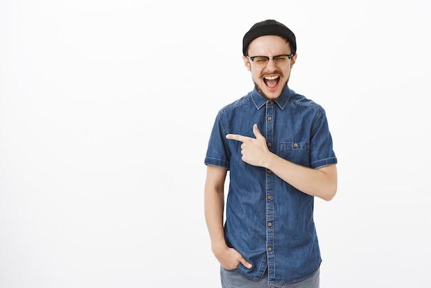 Indoor shot van opgewonden en geschokt knappe hipster bebaarde man in zwarte muts die hardop schreeuwt met gesloten ogen en geopende mond naar links wijzend, overweldigd door emoties over witte muur