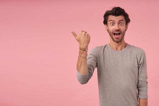 Indoor shot van opgewonden jonge man met trendy kapsel opzij wijzend met duim, vreugdevol kijken en wenkbrauwen optrekken, geïsoleerd