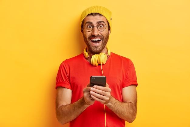 Indoor shot van optimistische blanke man downloadt nieuwe app voor het luisteren naar muziek op de mobiele telefoon, lacht naar de camera, bericht typen