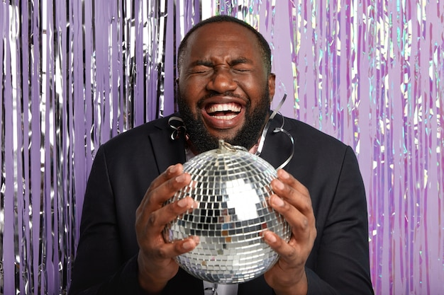 Indoor shot van optimistische dolgelukkige donkere man voelt zich vermaakt, lacht positief, houdt de ogen gesloten, draagt een elegant zwart pak, houdt discobal poses vast op een paarse muur met klatergoud. gevoel van vreugde