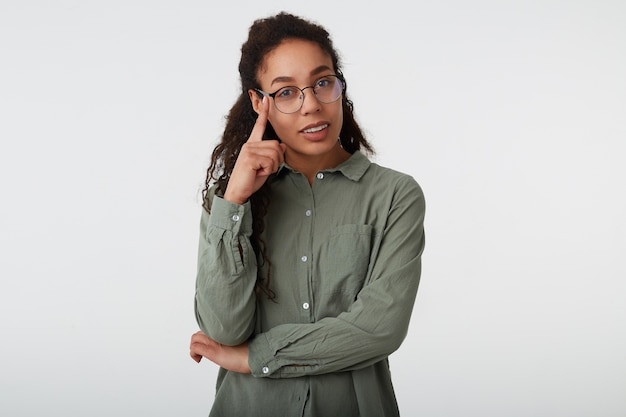 Indoor shot van positieve jonge bruinharige gekrulde vrouw met donkere huid houden opgeheven hand op haar brillen terwijl poseren op witte achtergrond in groen shirt