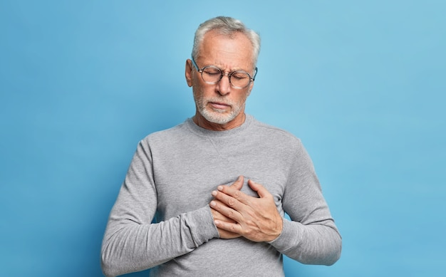 Indoor shot van senior bebaarde man heeft een hartaanval lijdt aan pijnlijke gevoelens heeft pijnstillers nodig drukt handen op de borst wordt ongezond draagt bril en grijze casual trui geïsoleerd op blauwe muur