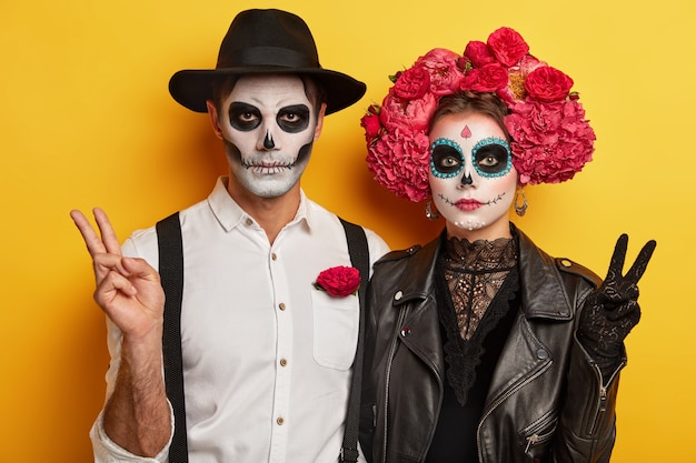 Indoor shot van serieuze vrouw en man in speciale enge kostuums, vredesoverwinningsgebaar maken, levendige make-up hebben om er vreselijk uit te zien, traditionele vakantie vieren in mexico
