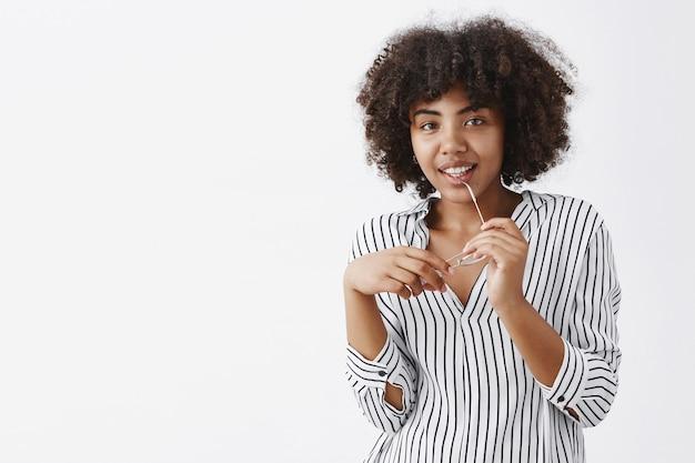 Indoor shot van speelse aantrekkelijke donkere vrouw met afro kapsel bijtende rand van bril en lachend met blij geamuseerde glimlach die iets wil zeggen maar verlegen is over grijze muur