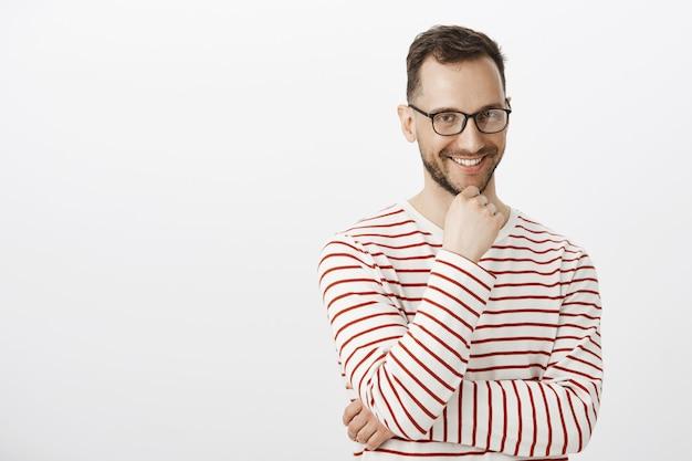 Indoor shot van speelse knappe man in zwarte bril, glimlachend met geïntrigeerde uitdrukking, met een interessant verlangen of intentie