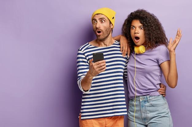 Indoor shot van stomverbaasd bang paar check nieuws op mobiele telefoon, staren in de verte, kijk naar vreselijke scène