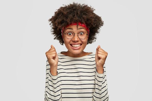 Indoor shot van succesvolle dolblij vrouw met donkere huid balde vuisten, heeft een stralende glimlach, kijkt met geluk, verheugt zich geslaagd voor examen, gekleed in gestreepte trui, poseert over witte muur