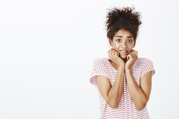 Indoor shot van timide onzekere vrouw met afro kapsel poseren in de studio
