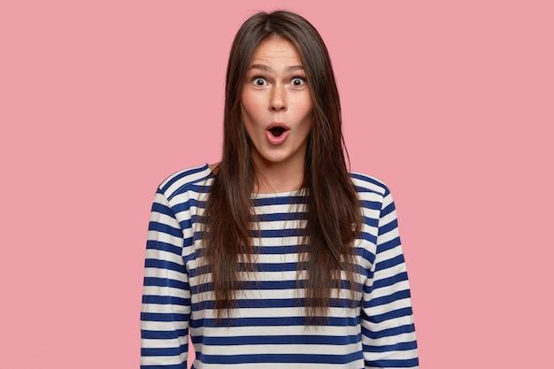 Indoor shot van verbaasd sproeten brunette vrouwelijk model opent mond met grote verbazing