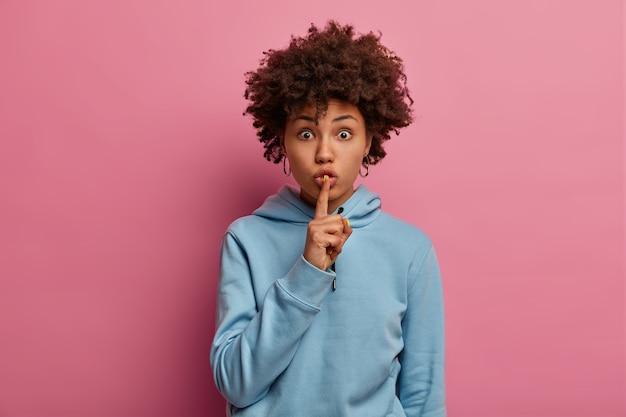 Indoor shot van verbaasde donkere vrouw heeft een geheim plan, maakt een stil gebaar, kijkt met een verbijsterde uitdrukking, draagt een blauwe hoodie, toont een stil of stil teken, poseert binnen over een roze muur.