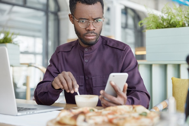 Indoor shot van verrast donkere huid afro-amerikaanse mannelijke ondernemer ontvangt slecht nieuws op slimme telefoon, staart naar het scherm, werkt aan zakelijk project op laptop