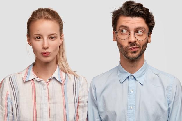 Indoor shot van vriendelijke gemengd ras vrouw en man gekleed in stijlvolle shirts, samen poseren tegen een witte muur, nadenken over een creatieve oplossing, samenwerken voor een gemeenschappelijke taak. broer en zus