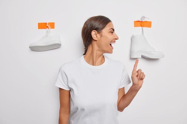 Indoor shot van vrolijke brunette vrouw wijst naar boot demonstreert schoenen voor het dragen van sneeuwwit schoeisel na het lopen gekleed in casual t-shirt poses alleen