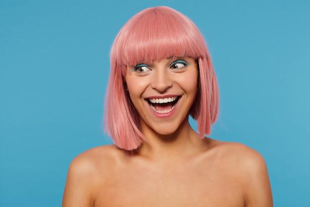 Indoor shot van vrolijke jonge mooie vrouw met roze bob kapsel opgewonden opzij kijken en breed glimlachen, feestelijke make-up dragen terwijl poseren op blauwe achtergrond