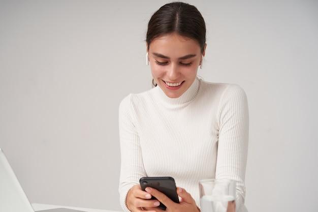Indoor shot van vrolijke jonge vrij donkerharige vrouw met paardenstaart kapsel mobiele telefoon in opgeheven handen houden en kijken naar het scherm met een gelukkige glimlach, geïsoleerd over witte muur