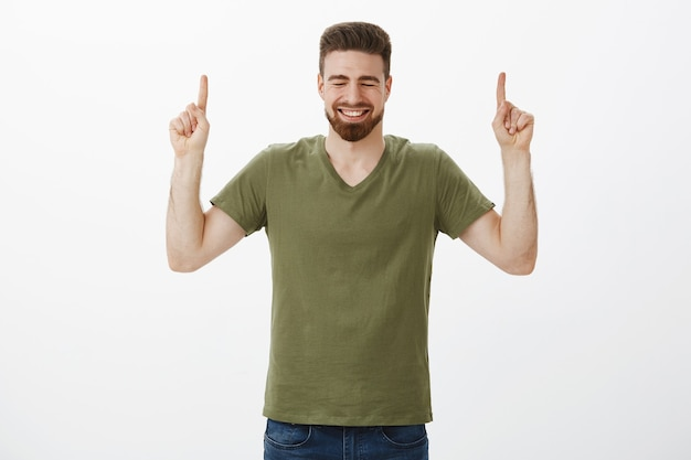 Indoor shot van zeer gelukkige knappe bebaarde vriend juichen en zich vrolijk voelen glimlachen giechelend met gesloten ogen als wijzend met opgeheven wijsvingers omhoog tegen een witte muur