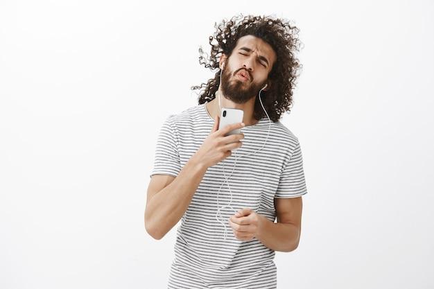 Indoor shot van zorgeloze emotionele bebaarde man in stijlvolle outfit, smartphone in de buurt van gezicht te houden