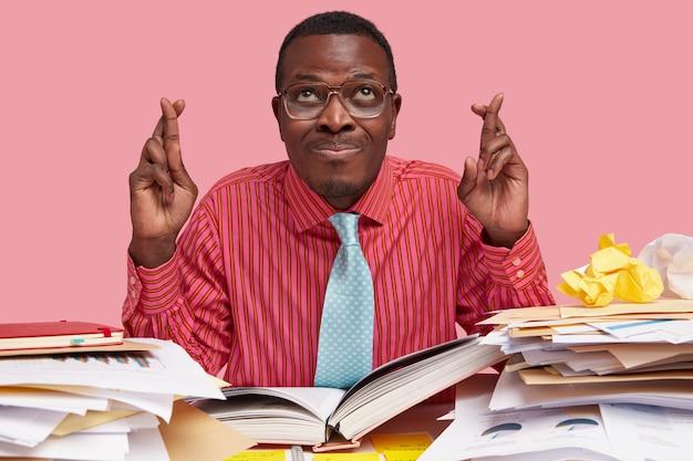 Indoor shot van zwarte man heeft grote hoop, kruist vingers voor geluk voor het examen, draagt elegante kleding