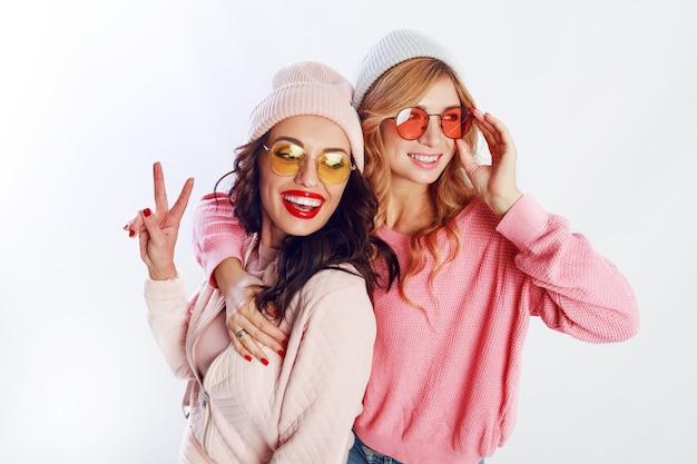 Indoor studio afbeelding van twee meisjes, gelukkige vrienden in stijlvolle roze kleding en hoed spelling grappig samen. witte achtergrond. trendy hoed en bril die vrede tonen.