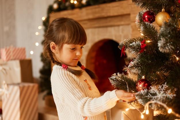 Indoor studio-opname van charmant meisje met witte trui en staartjes, kerstboom versieren, in de buurt van open haard staan, feestelijke stemming hebben.