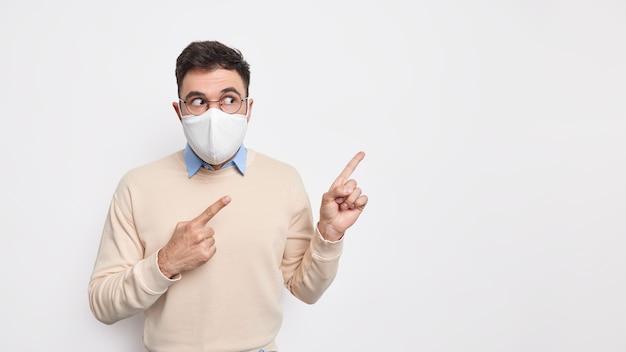 Indoor studio-opname van geschokte volwassen man draagt beschermend gezichtsmasker om te voorkomen dat coronavirus de gezichtsuitdrukking heeft verrast