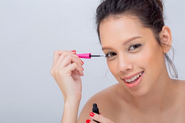 Indoor studio-opname voor mooie blanke vrouw glimlachend breed zwarte mascara toe te passen op wimpers