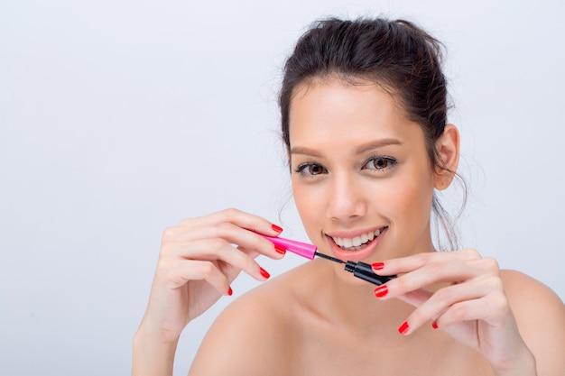 Indoor studio-opname voor mooie blanke vrouw lachend in grote lijnen zwarte mascara toe te passen op wimpers met schoonheid aard make-up frisse zachte huid